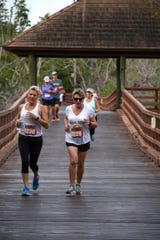 "Angela Segler, left, and Allyson Richards cross the mangroves. The Kiwanis Club of Marco Island hosted its 6th Annual 5K Run/Walk, called ""Running for Kids,"" on Saturday 12/1/18 through the Hideaway Beach community."