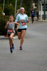 Regan O'Donnell puts on a burst of speed to finish during the Kiwanis Club of Marco Island's 6th Annual 5K Run/Walk on Saturday.