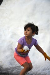 Sofia Gazieya, 3, prepares to throw her first snowball. Thousands of children and their parents came out for a taste of winter at Snowfest, Saturday afternoon at Golden Gate Community Center.