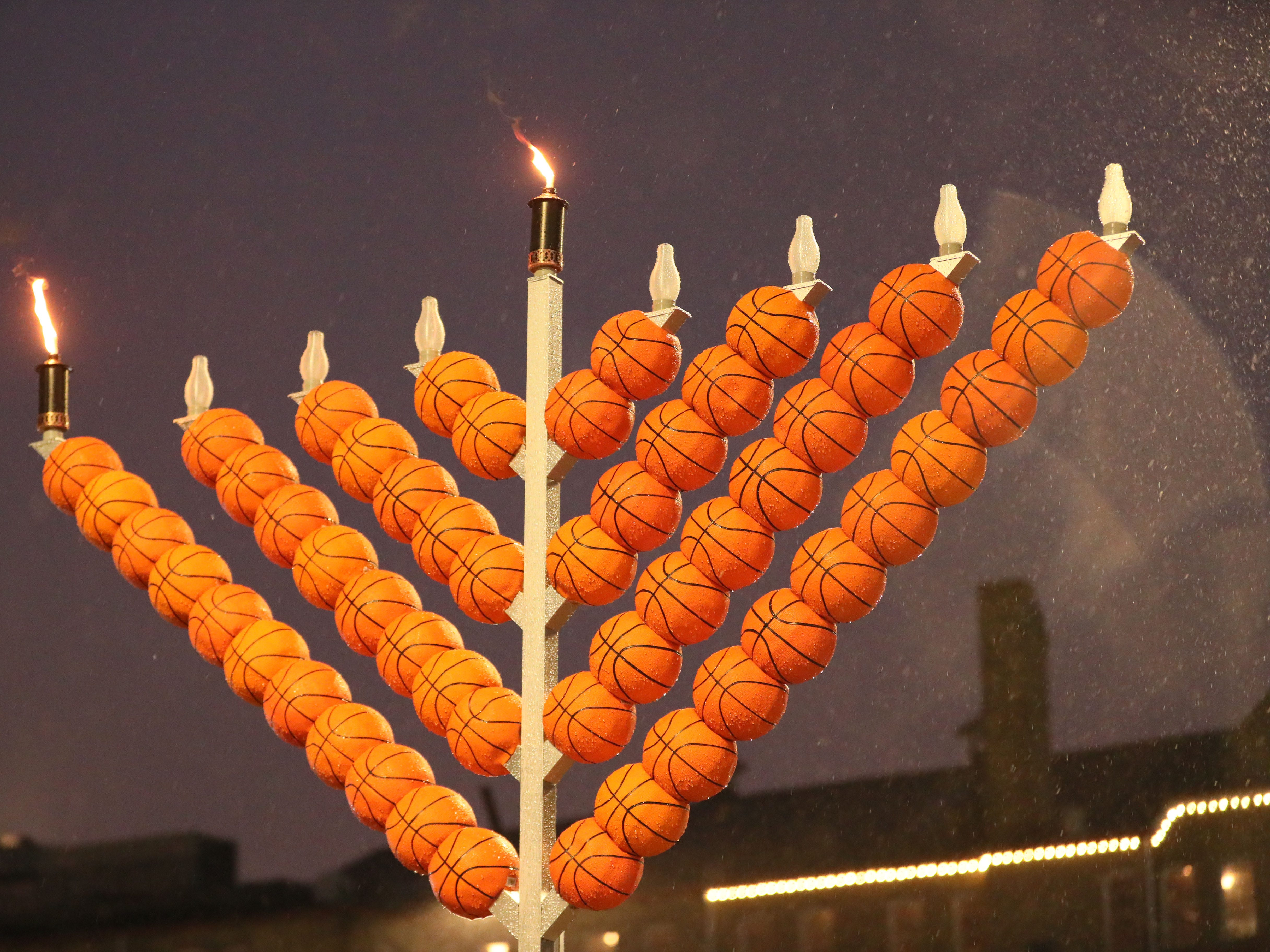 The basketball-themed menorah stands lighted against the skyline as rain and snow fall.