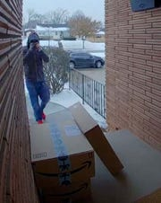 A home surveillance camera captured this image of a suspect in about 175 instances of package theft eyeing up a couple packages waiting outside a home in Greenfield.