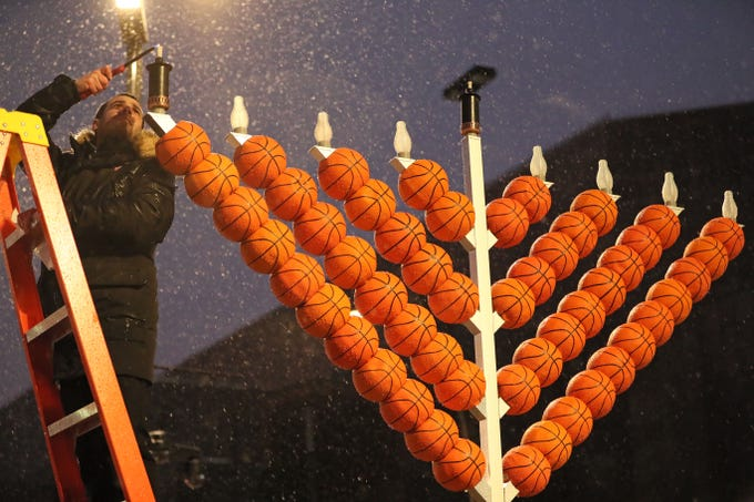 Bucks Senior Vice President Alex Lasry struggles against rain and snow to get the Hanukkah menorah lighted.  It later had to be lighted again with a torch. Fiserv Forum held a public lighting ceremony on the plaza Sunday.  Rabbi Mendel Shmotkin and Lasry spoke at the event. Chabad-Lubavitch of Wisconsin was also involved.