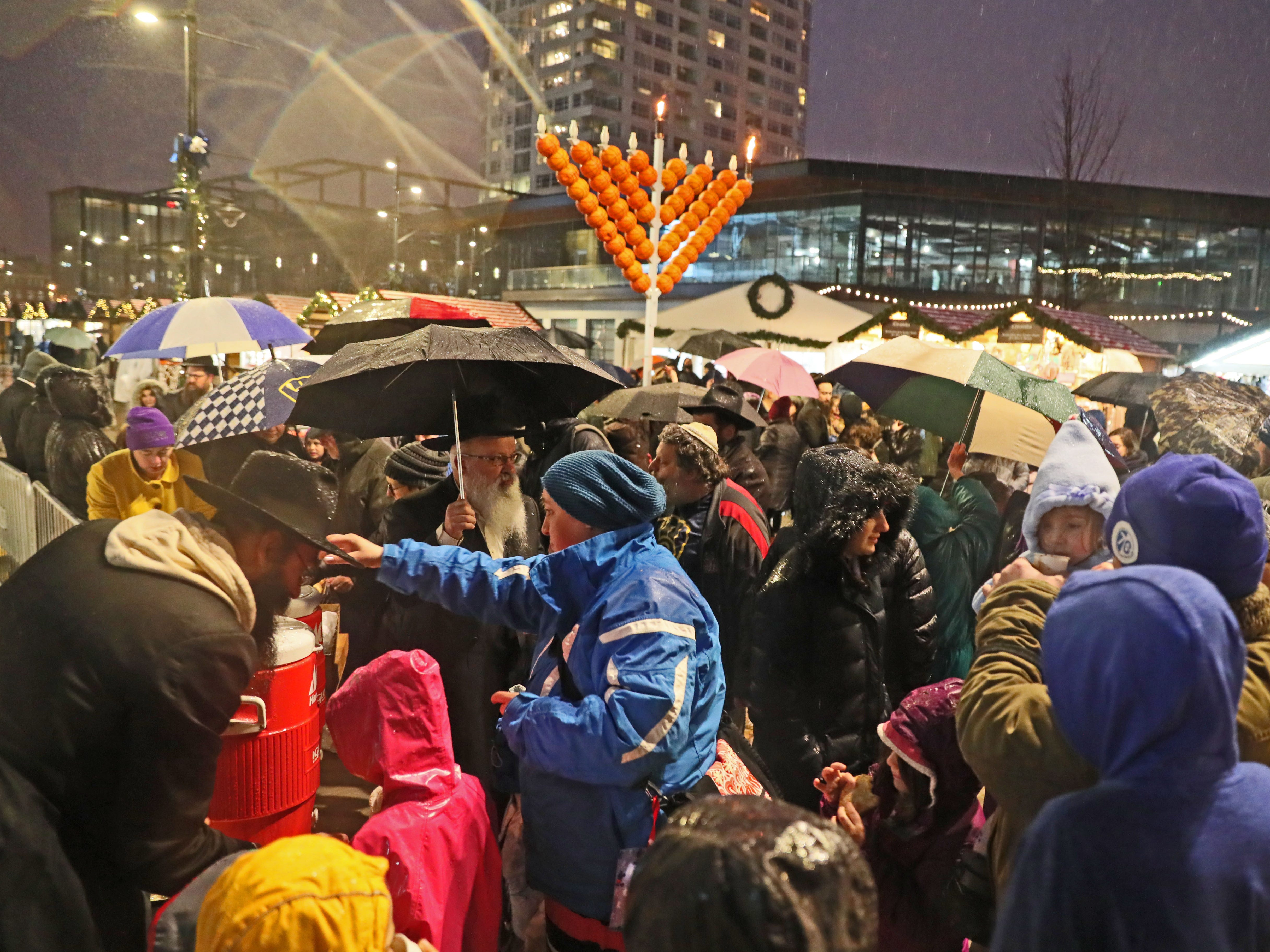 Children and adults gather for hot chocolate after the menorah lighting ceremony on the plaza at Fiserv Forum.