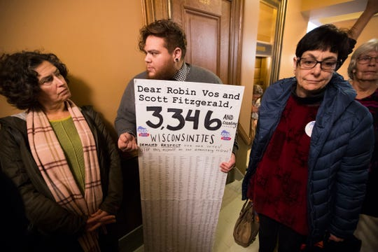 People protest Monday in the Capitol about the lame-duck session in which Republican lawmakers are considering legislation to limit the powers of Governor-elect Tony Evers.