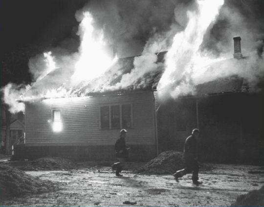 Firefighters combat the blaze from the burning Freedom House
