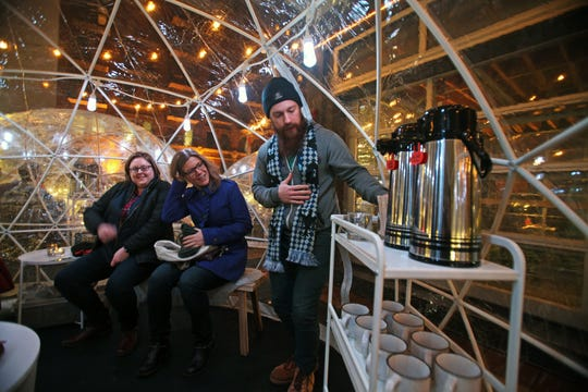 Joe Moeller (right), a server at Cafe Benelux in Milwaukee's Third Ward, explains to Emily Ristow (left) and Erin Richards (center) the beverage and food situation in one of the restaurant's Lux Domes on its opening night, Nov. 30, 2018.