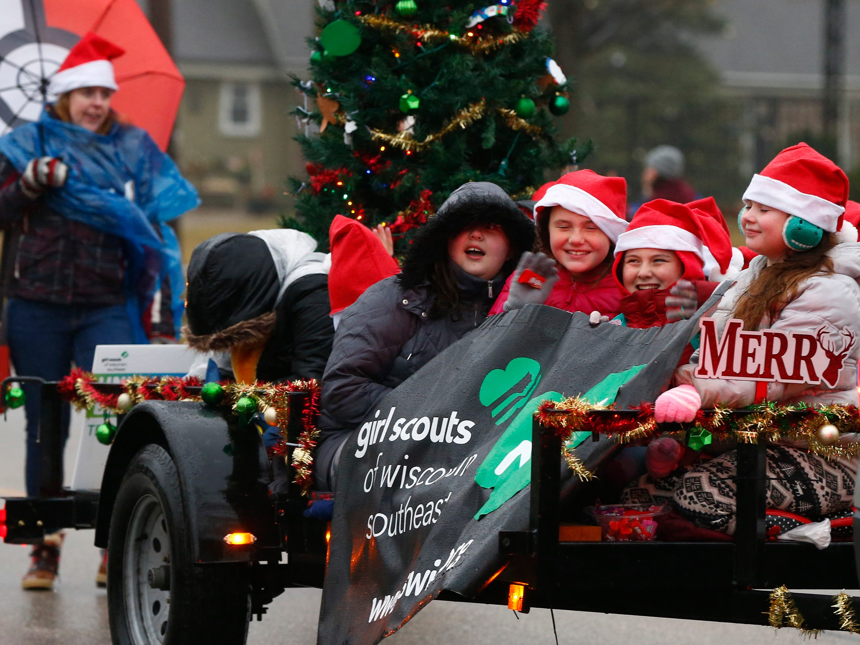 Girl Scouts try to stay dry while riding a float during the first city-sponsored St. Francis Christmas Parade on Dec. 1.
