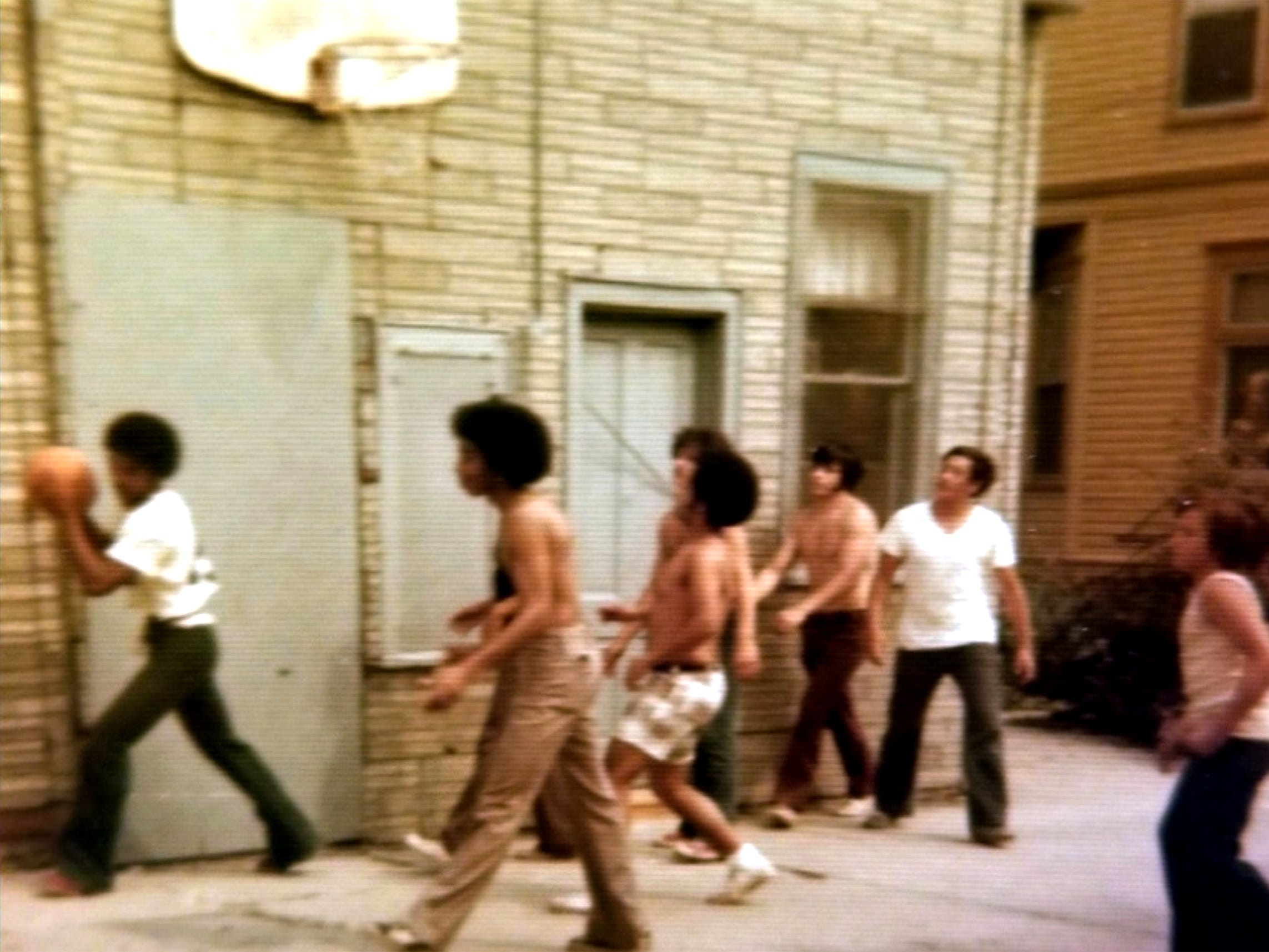 """Teens shoot hoops in Bob Paquette's """"community gymnasium"""" behind his home in Merrill Park during the 1970s."""