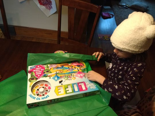 Five-year-old Harper Brown prepares a gift she picked out for a holiday wish list project.