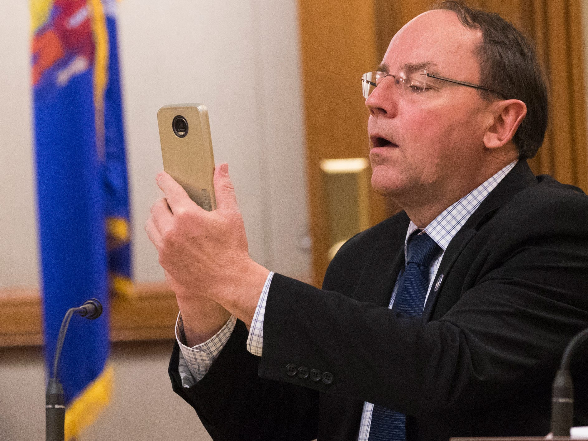 State Sen. John Tiffany (R-Hazelhurst) takes a photo of a protester during the Joint Finance Committee hearing Monday.