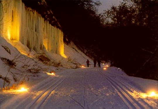 An icefall along the Red Cedar State Trail south of Menomonie is illuminated during a candlelight ski event.