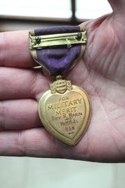 Ken Mater shows his uncle Roy K. Marin's Purple Heart.