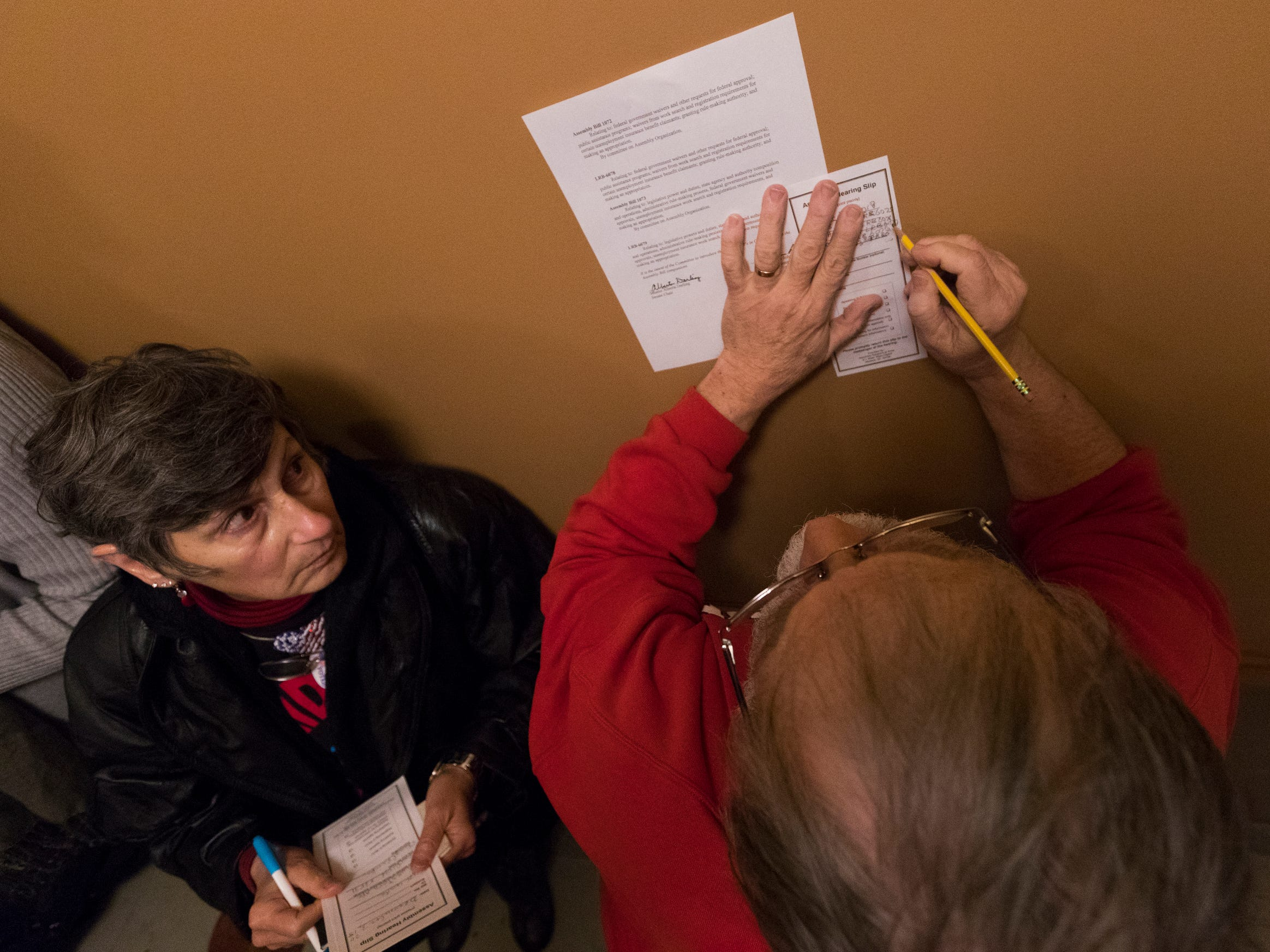 People fill out slips to speak before the Joint Finance Committee Monday, Dec. 3, 2018, at the Capitol in Madison, Wis.