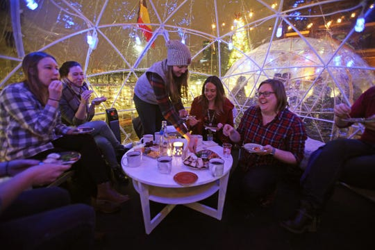 A group of women enjoys food and drinks inside one of Cafe Benelux's Lux Domes on the domes' opening night, Nov. 30, 2018.