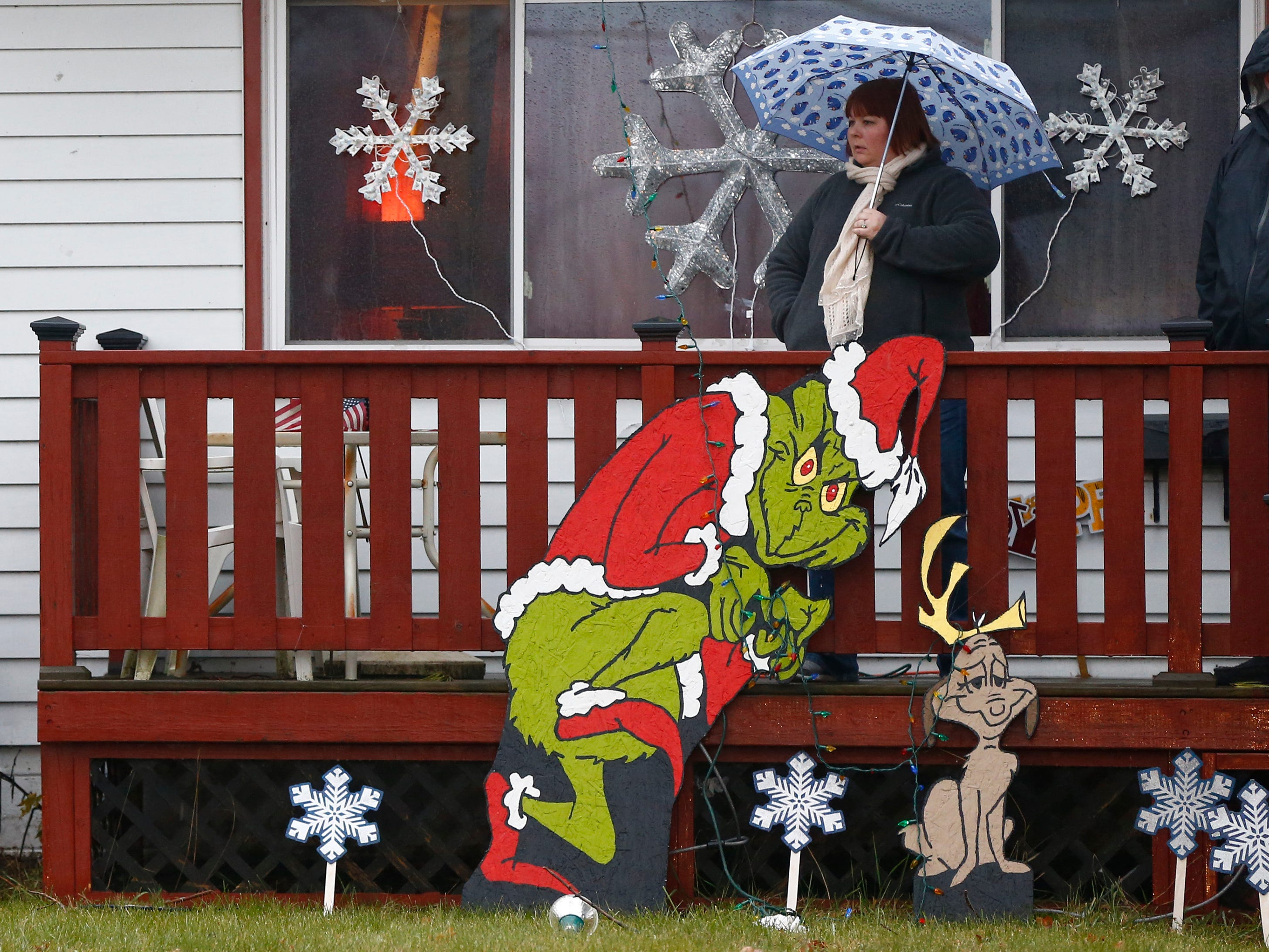 A parade watcher stays dry on her porch during the first city-sponsored St. Francis Christmas Parade on Dec. 1.