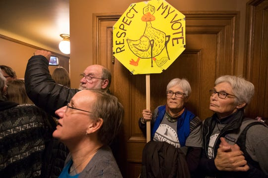 People crowding a hallway vent their anger outside a lame-duck session of the Joint Finance Committee Monday.