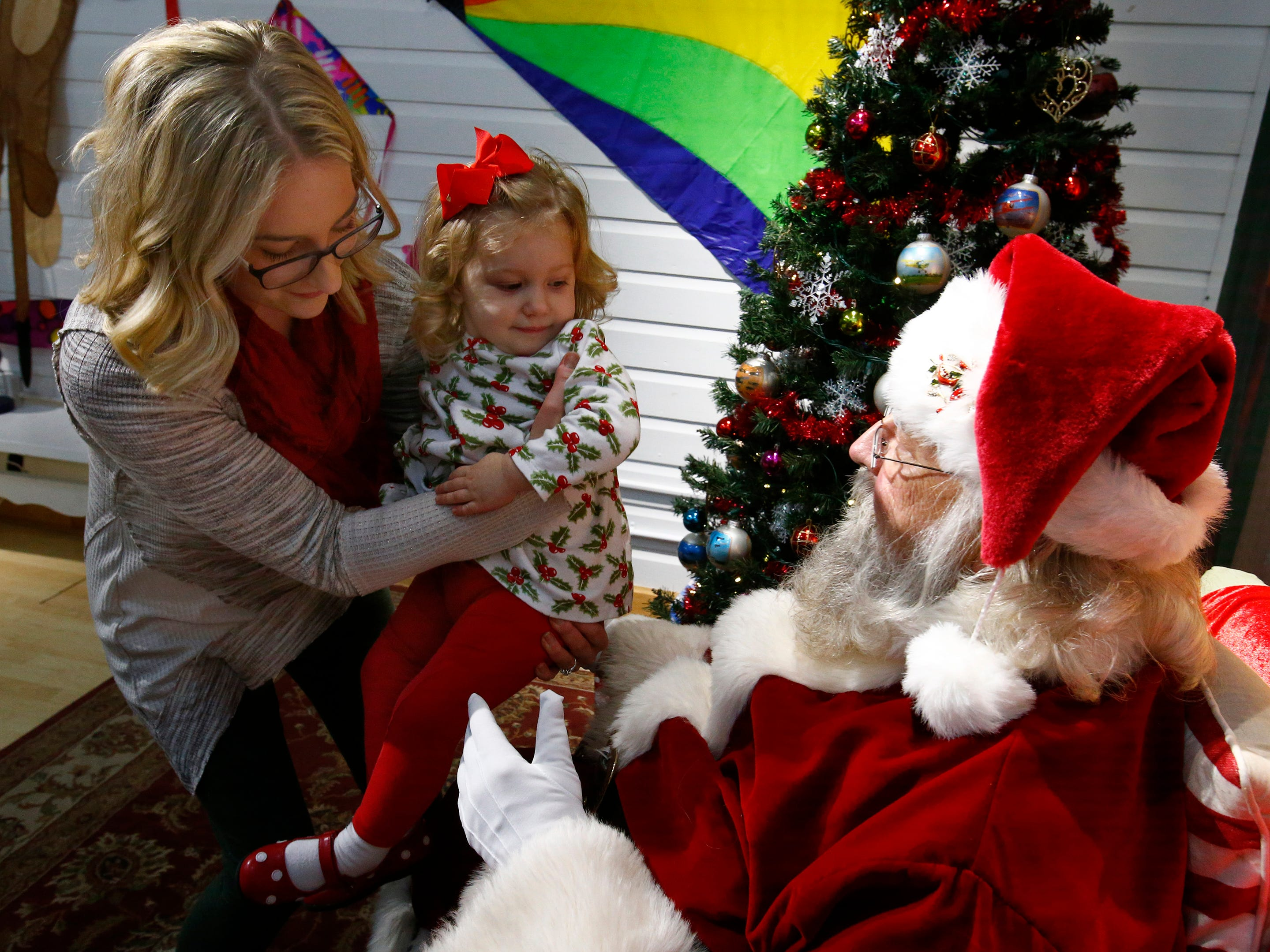 Karen Kurtz helps daughter Eleanor up for a visit with Santa at Gifts of Wings during Greendale's Dickens of a Christmas Festival on Nov. 30.
