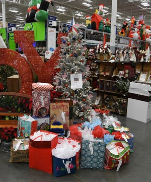 Christmas gifts sit underneath the Veterans Tree at the Mountain Home Lowe's home improvement store Monday. Store employees recently organized an angel tree-style program to benefit local veterans.