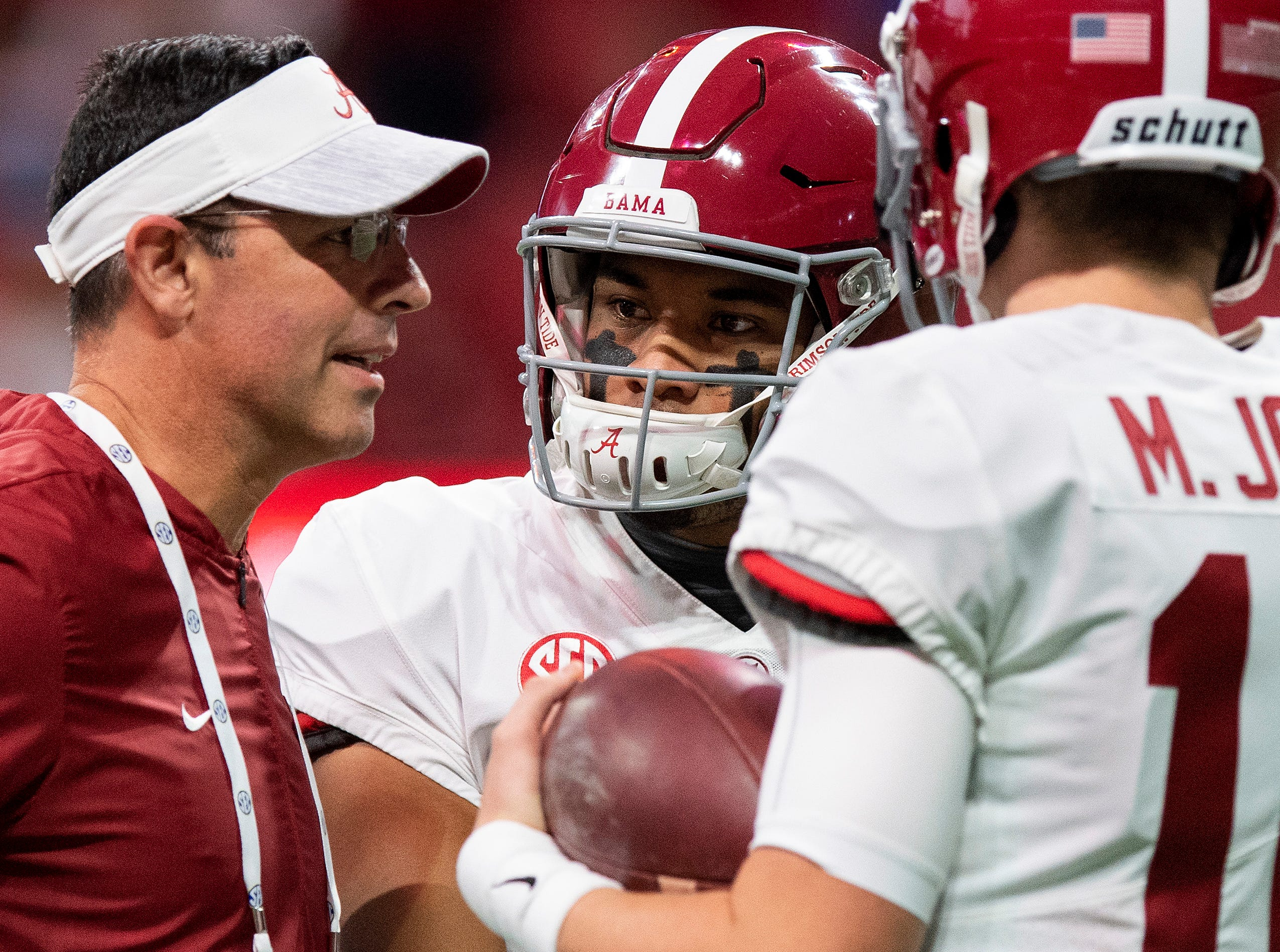 Alabama quarterbacks coach Dan Enos talks with quarterbacks Tua Tagovailoa (13) and Mac Jones (10) during warmups before the SEC Championship Game at Mercedes Benz Stadium in Atlanta, Ga., on Saturday December 1, 2018.