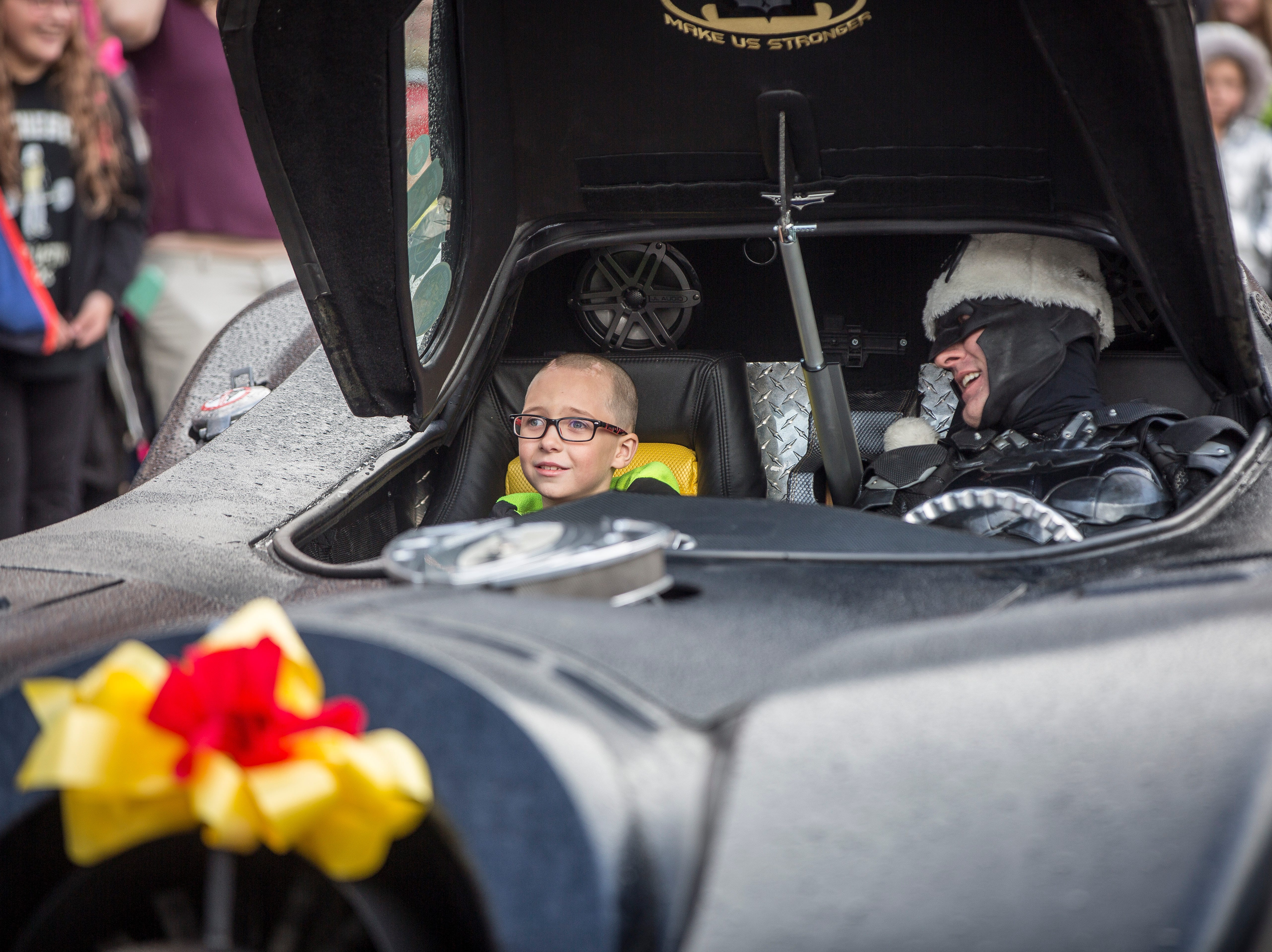 Christian Daugherty, a young Albany boy who was diagnosed with brain cancer, climbs into the Batmobile with John Buckland dressed as Batman. The organization H4H Foundation helps provide last wish Batmobile rides to youth who are terminally ill and more.