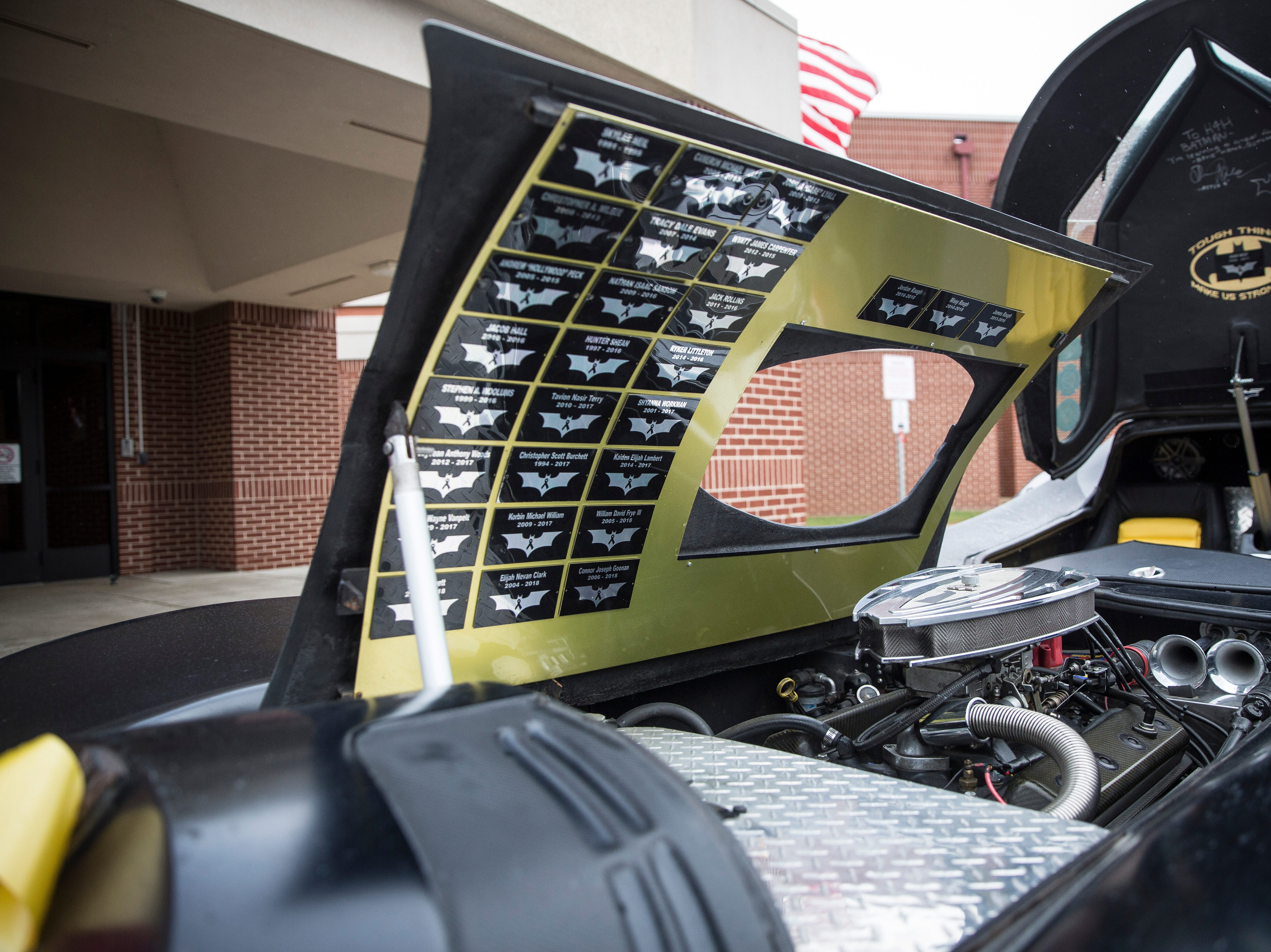 Plaques on the inside of the Batmobile hood recognize children that the H4H Foundation have served as pallbearers with. Many of the children have ridden in the Batmobile before passing away.