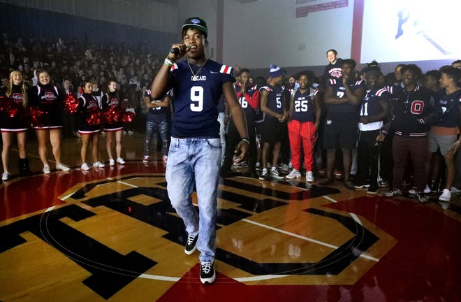 Oakland football player, senior Tekoy Randolph (9), speaks to the student body during a pep rally Monday at the school.