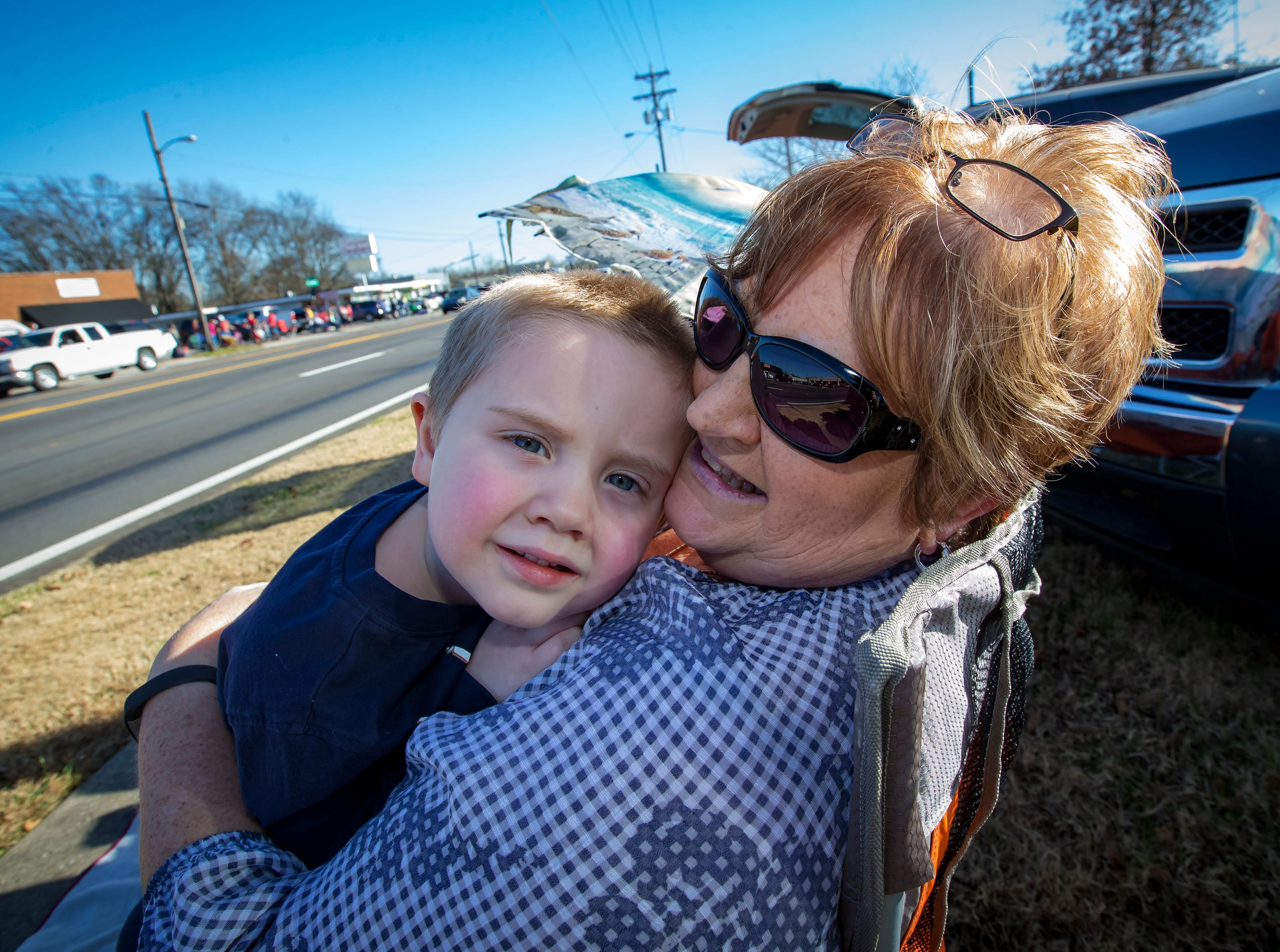 Elijah Norman cuddles with his grandmother Dianne Norman as they wait for the start of the Smyrna Christmas parade.