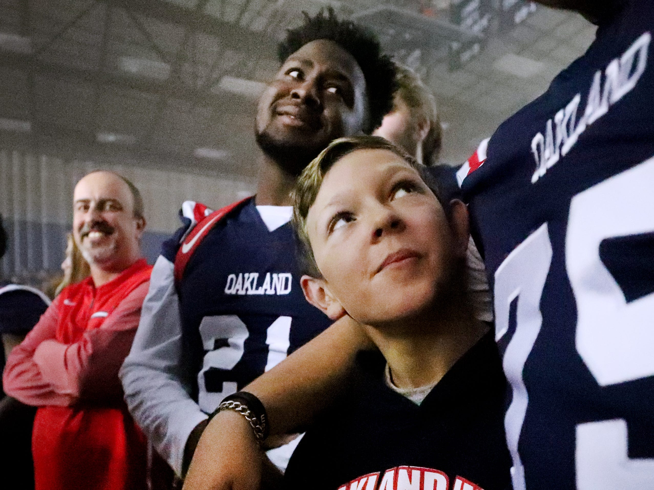 Kyler Creasy, the son of Oakland High School head football coach Kevin Creasy, looks up at Oakland player Kain Williams (75) during a pep rally, on Monday, Dec. 3, 2018 at the school after the football team won the 6A State Championship BlueCross Bowl game against Westhaven on Thursday.