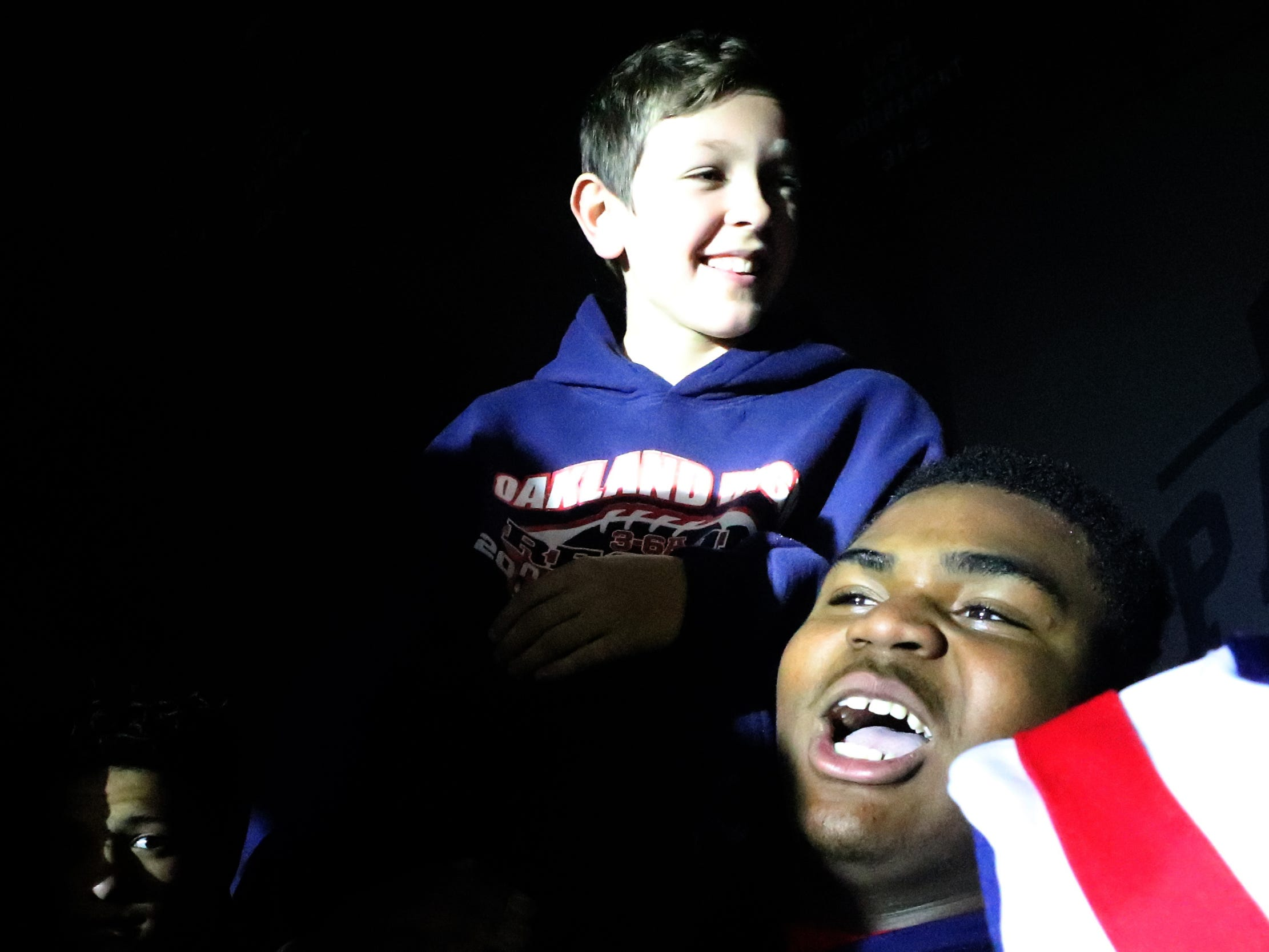Oakland High School Kylan Spencer (99) holds up Kyler Creasy, the son of the football head coach Kevin Creasy, during a pep rally, on Monday, Dec. 3, 2018 at the school after the football team won the 6A State Championship BlueCross Bowl game against Westhaven on Thursday.