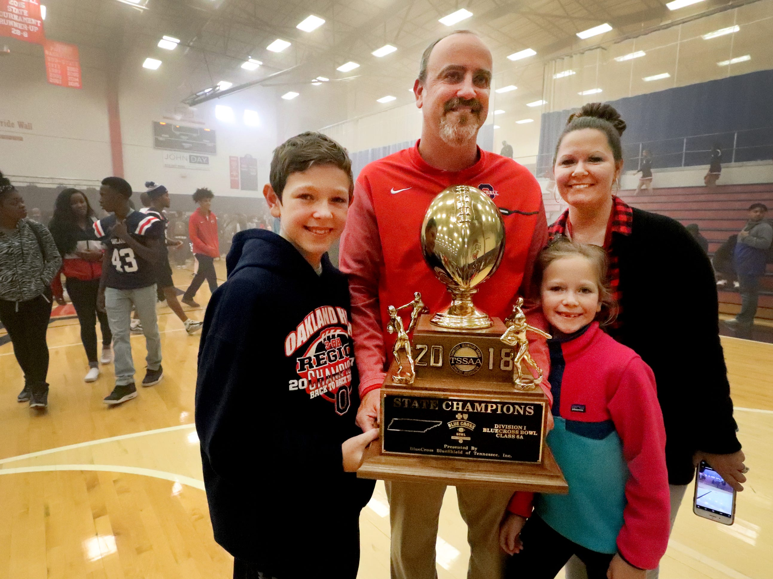 The Oakland High School head coach Kevin Creasy Creasy with his family son Kyler, daughter Kinley and wife Katie with the state championship trophy after a pep rally, on Monday, Dec. 3, 2018 at the school after the football team won the 6A State Championship BlueCross Bowl game against Westhaven on Thursday.