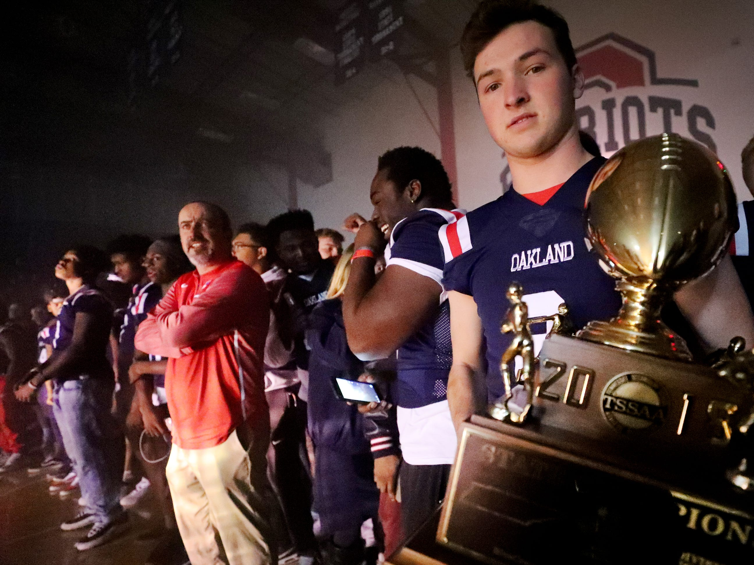 Oakland's quarterback Brevin Linnell (2) hold the trophy as he stands with the team as Oakland High School holds a pep rally, on Monday, Dec. 3, 2018 at the school after the football team won the 6A State Championship BlueCross Bowl game against Westhaven on Thursday.