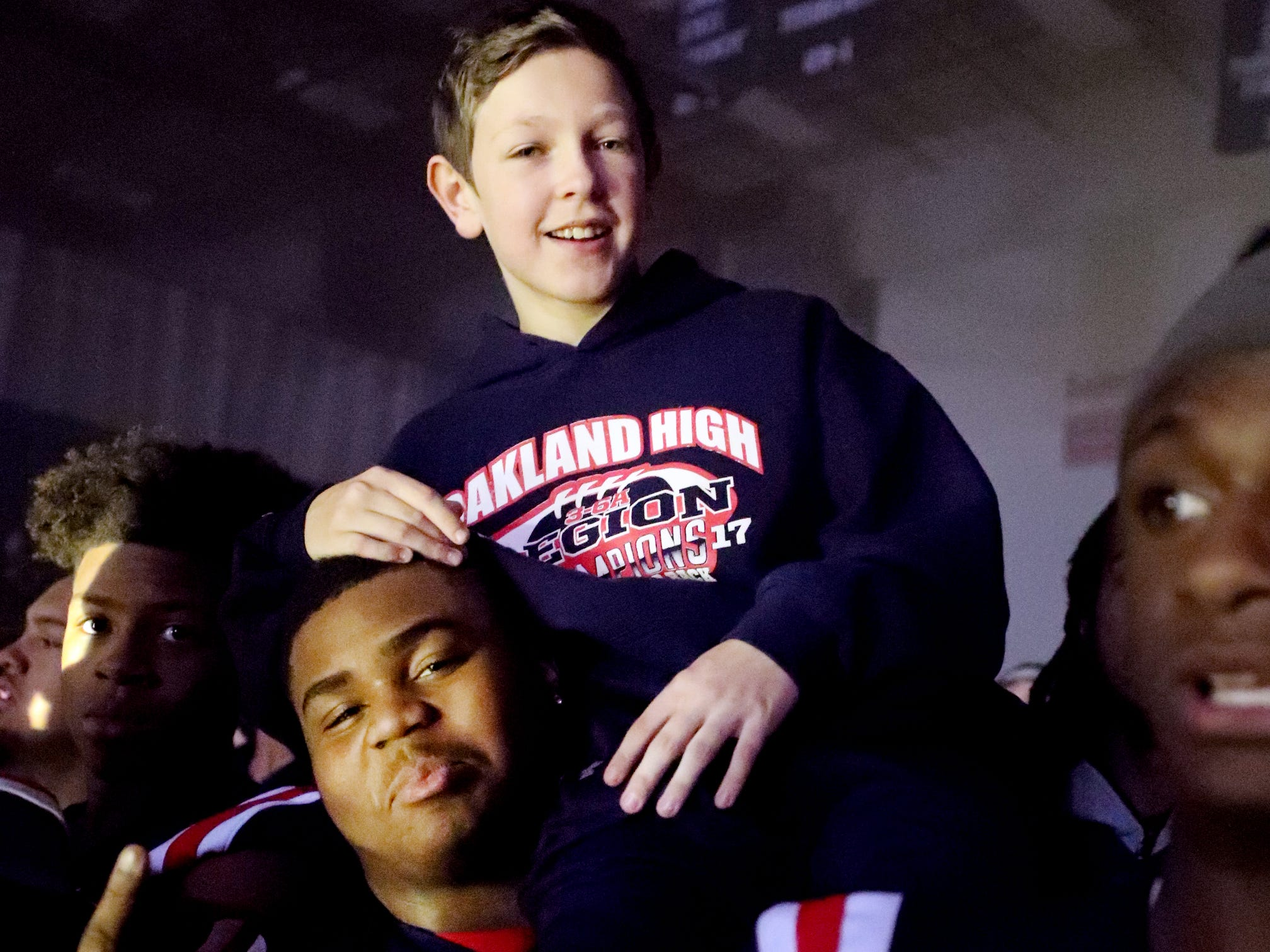 Oakland High School's  Kylan Spencer (99) holds Kyler Creasy, the son of Oakland head coach Kevin Creasy during a pep rally, on Monday, Dec. 3, 2018 at the school after the football team won the 6A State Championship BlueCross Bowl game against Westhaven on Thursday.
