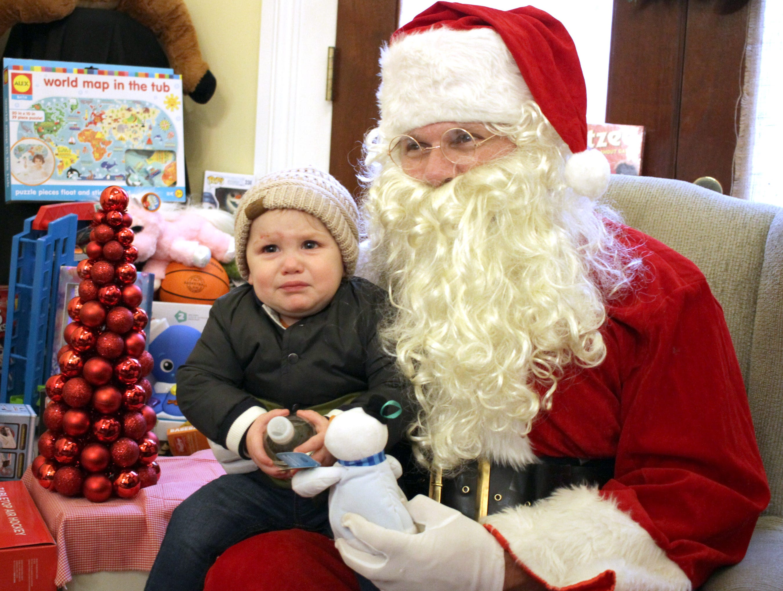 Fifteen month old Connor Fish isn't too happy meeting Santa Claus at before the Christmas parade in Ashland City, on Saturday, December 1, 2018.