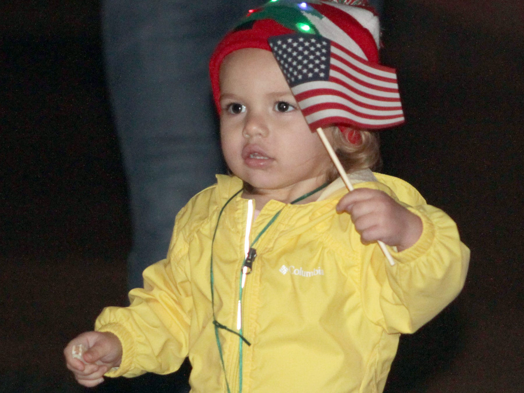 A young child waves her flag at the Ashland City Xams parade on Saturday, December 1, 2018.