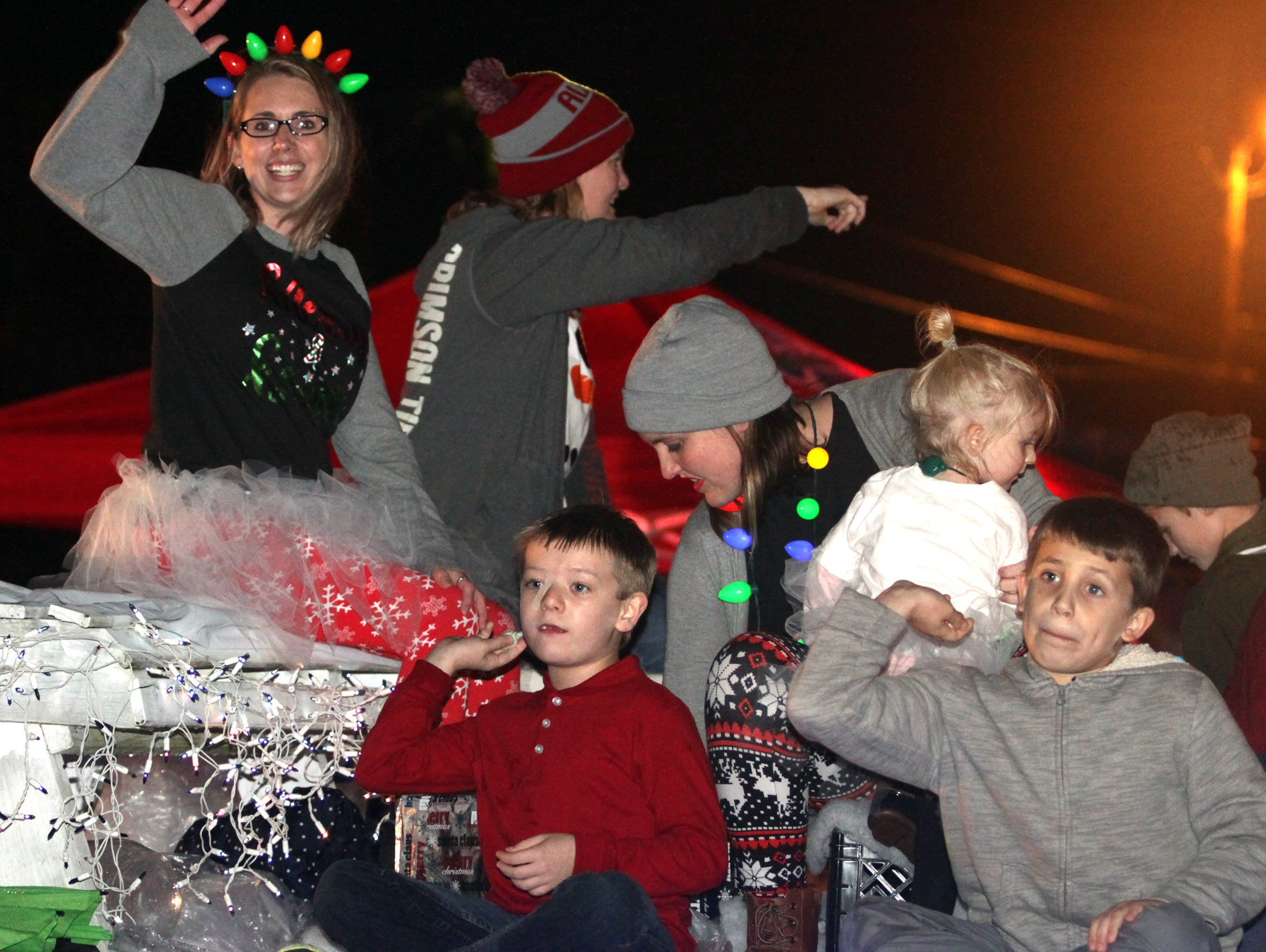 Children ride and throw candy from a float at the Ashland City xmas parade on Saturday, December 1, 2018.