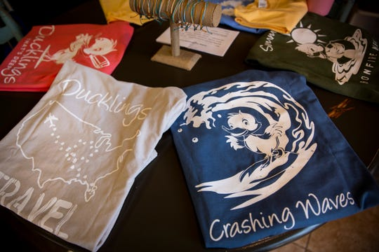 Shirts designed by Taylor Bouchard sit on a table for sale during a fundraiser on Sunday, December 2, 2018, at Aerie Lane in Bonita Springs.