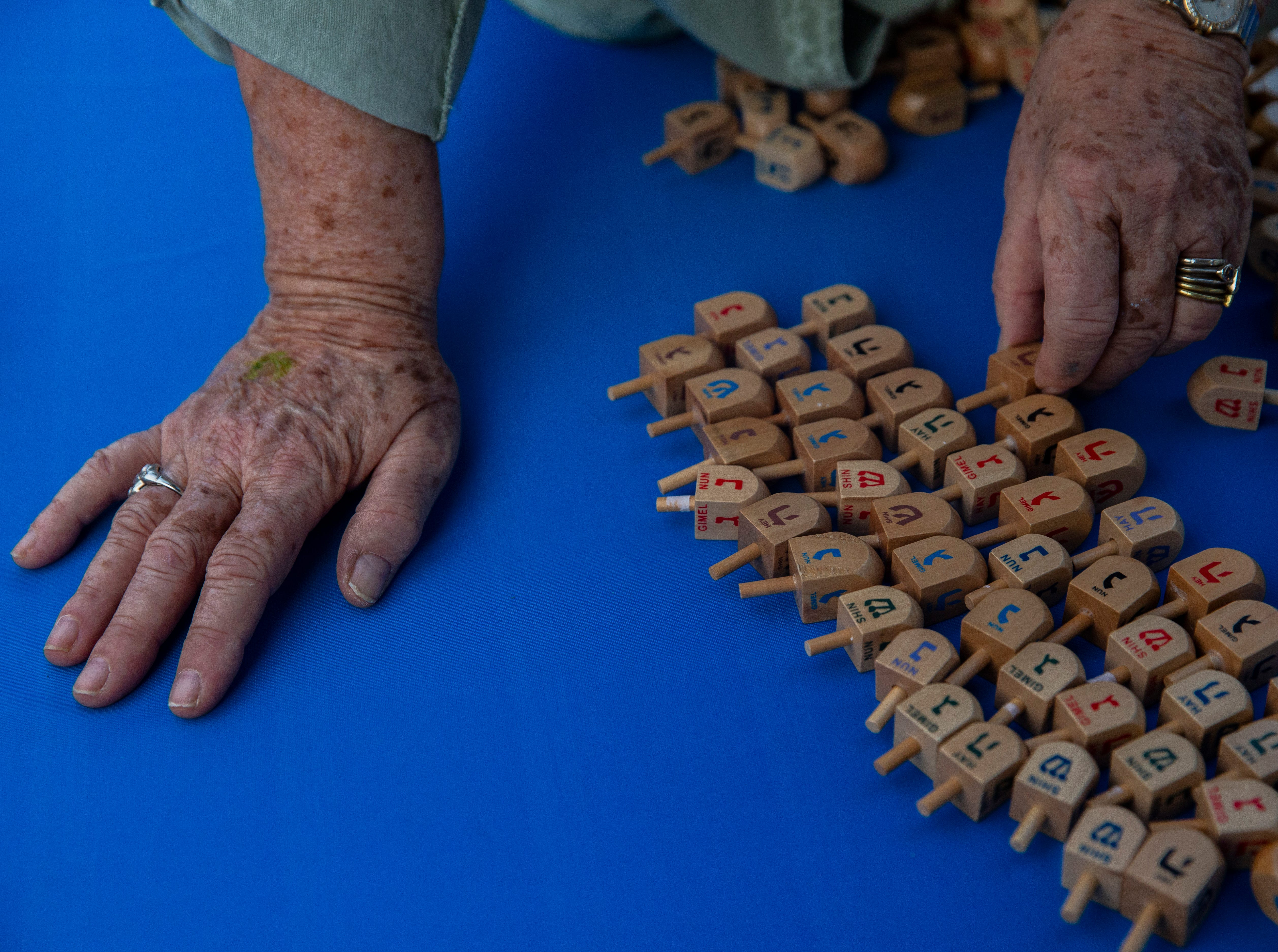 Linda Simon, with the Woman's Cultural Alliance of Naples, arranges wooden dreidels for a children's game at their stall called Spin the dreidel and win a prize, during the 20th annual Hanukkah celebration at the Mercato Lawn on Monday, Dec. 3, 2018, organized by the Jewish Federation.