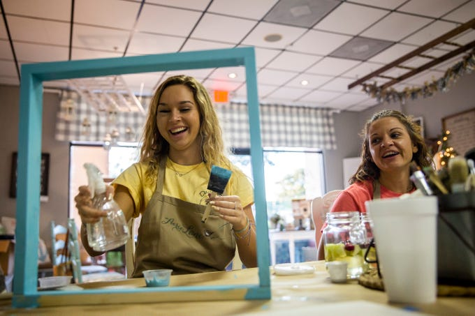 Taylor Bouchard, a senior at Estero High School, and her mother Emily Bouchard laugh as Taylor paints a frame during a fundraiser for their nonprofit, Ducklings Travel, that aims to financially help families who have to travel for medical care for their children on Sunday, December 2, 2018, at Aerie Lane in Bonita Springs. Taylor was diagnosed with an arteriovenous malformation in her face when she was 10 and has had to travel to Colorado for treatment over the past seven years.