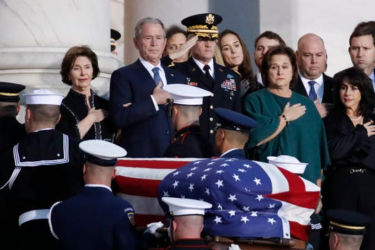 Former President George W. Bush, second from left; Laura Bush, left, and other family members watch as the flag-draped casket of former President George H.W. Bush is carried by a joint services military honor guard to lie in state in the rotunda of the U.S. Capitol on Monday, Dec. 3, 2018, in Washington.