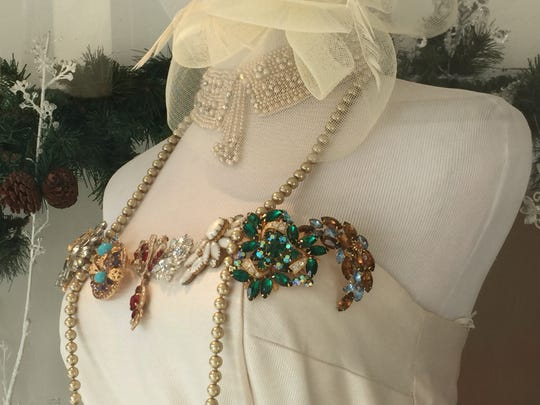 The cream-colored bodice is decorated with antique pins.