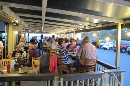 Outdoor dining on the porch in front of the new Bonita Beach Balloon Bar & Grill on Bonita Beach Road in Bonita Springs.
