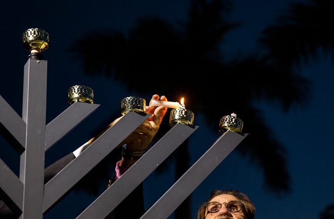 Rabbi Howard Herman, of the Naples Jewish Congregation, lights up the menorah during the annual Hanukkah at the Mercato Lawn on Monday, Dec. 3, 2018, organized by the Jewish Federation.