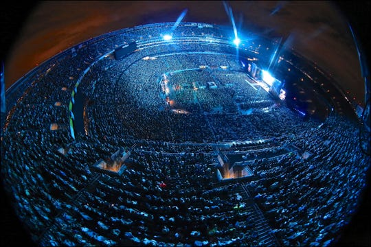 In this Aug. 18, 2018 photo taken with a fisheye lens and provided by Essential Broadcast Media, country music star Kenny Chesney fills MetLife Stadium during a concert in East Rutherford, N.J.