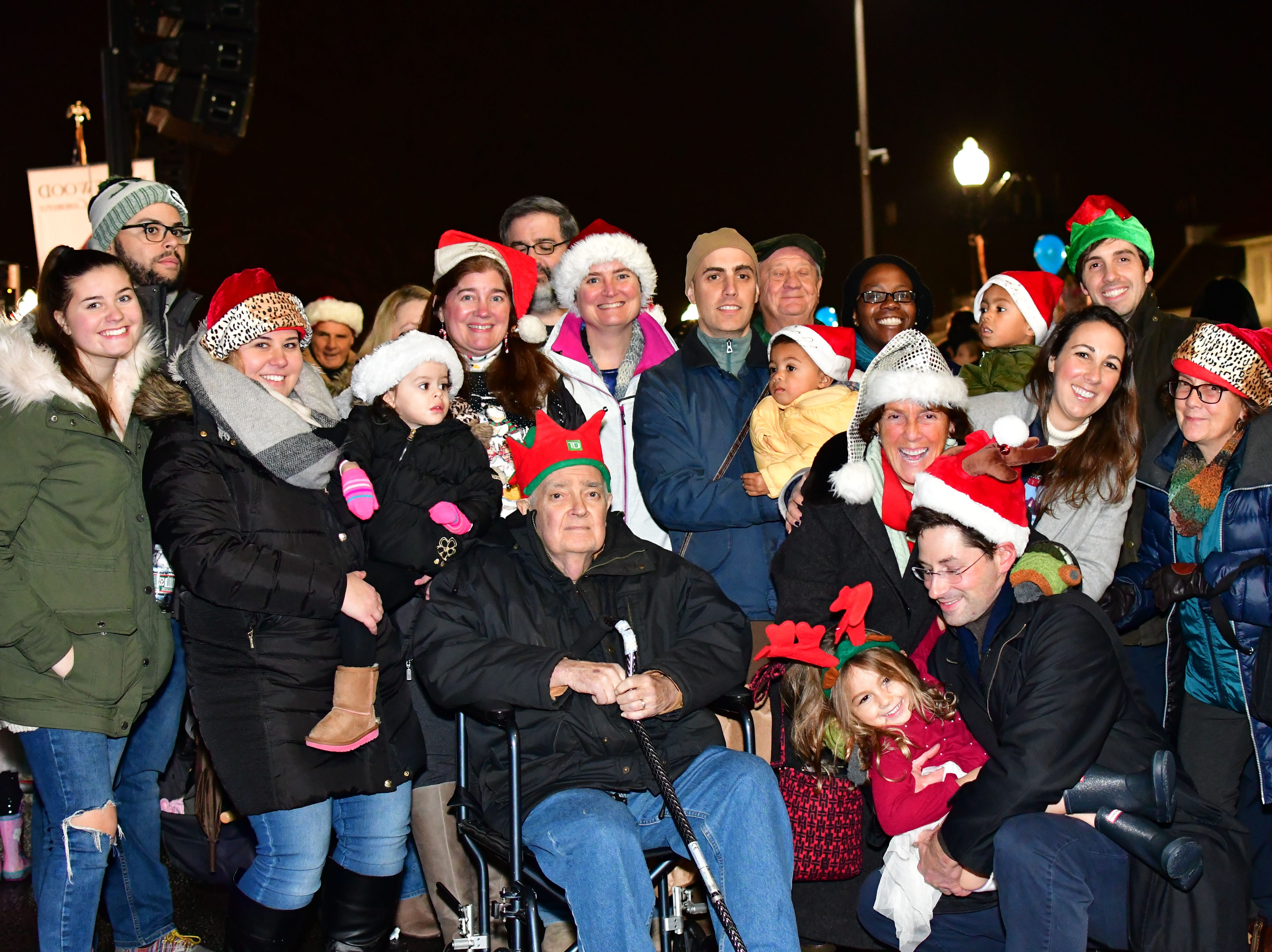 Justine Clinch Kaufman, far right, jacket. To her left is Janel Clinch, the tree dedicated to her husband Carleton Clinch who passed.  Holiday festivities along East Ridgewood Avenue in Ridgewood on Nov. 30.