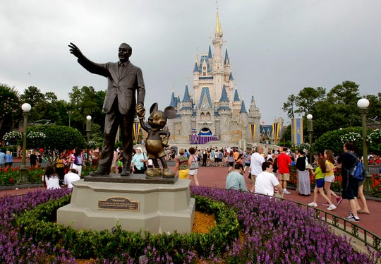 """Visitors stroll on Main Street at Walt Disney World in Florida. Psychologist Anne Rothenberg said parents should not feel pressured to buy this type of expensive """"experience"""" gift."""