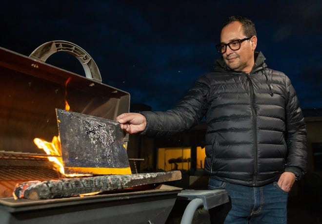 Artist Michael Poncé places a piece of his artwork in a fire Sunday, Dec. 2, 2018, during a closing reception for a recent exhibit. Poncé decided to destroy all of the artwork that was not sold.