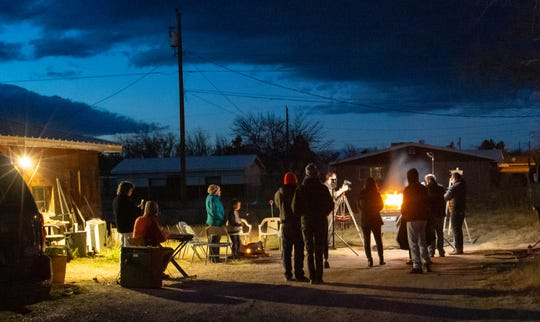 A group gathers as artist Michael Poncé sets his artwork on a fire Sunday, Dec. 2, 2018, during a closing reception for his recent exhibit. He destroyed about 10 pieces of art.