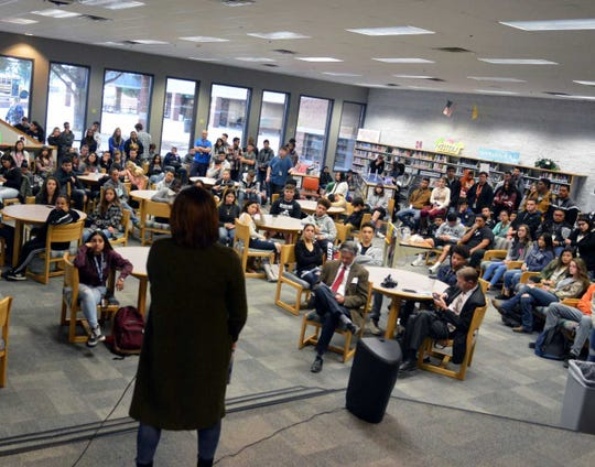Oñate High School government students listen to Stephanie Valencia — an alum of the school and a staffer at the White House during the Obama Administration — during an event in the school's library on Monday, Dec. 3, 2018.