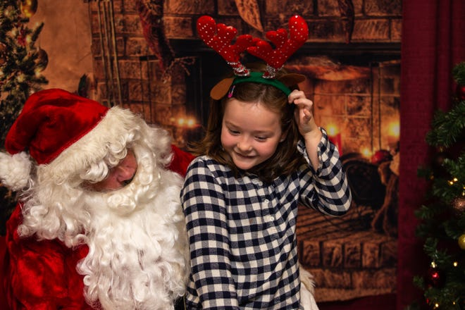 Amelia Janer, 7, lets Santa know what's on her Christmas gift list during the Noche de Luminarias event Sunday, Dec. 2, 2018, at New Mexico State University.