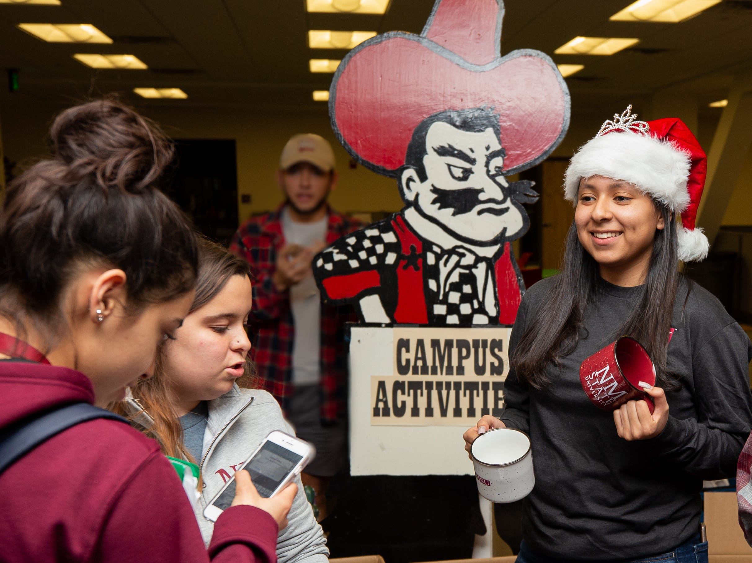 Misa Montalvo with NMSU Campus Activities hands out free T-shirts and mugs to NMSU students during the Noche de Luminarias event Sunday, Dec. 2, 2018, at New Mexico State University.